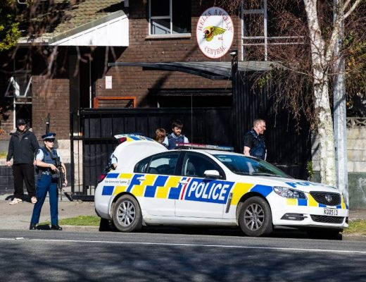 Armed police stand guard at the Hells Angels headquarters in Palmerston North while colleagues search the property. Credits: Stuff