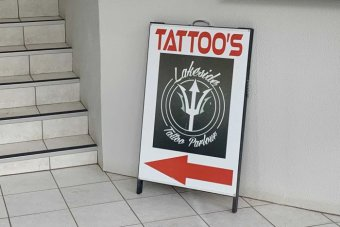 "A sign advertising ""tattoo's (sic.)"" folded up against a wall."