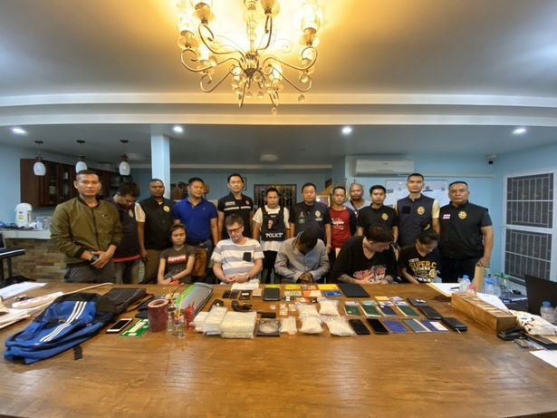 Police posing with a table full of illegal items