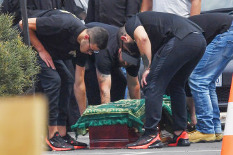 Nabil Maghnie's sons stand over his coffin.