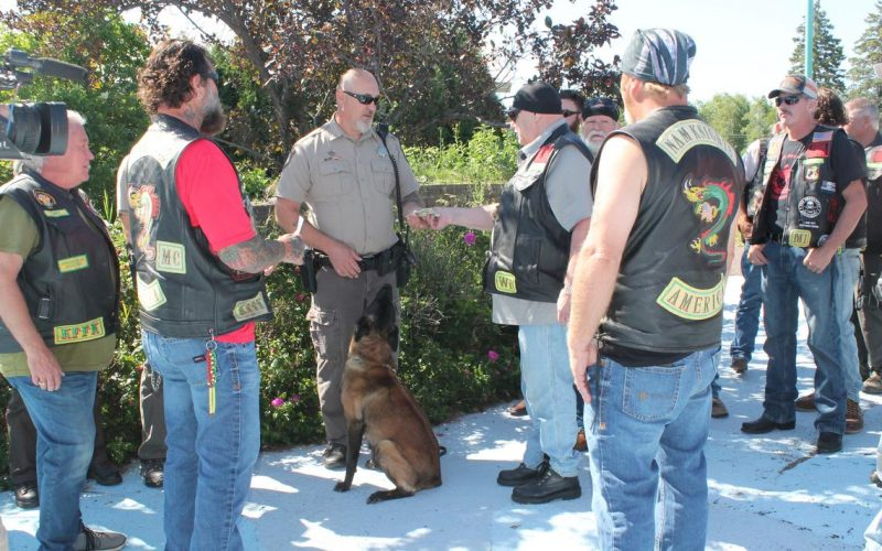 Douglas County Sheriff's Deputy Brian Witt, center left, and his partner, Talon, accept a donation from Ernest Bloomquist, center right, president of the Arrowhead Chapter of the Nam Knights of America motorcycle club July 10 at Harbor View Park near the Richard I. Bong Veterans Historical Center. (Maria Lockwood )