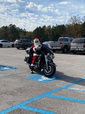 Santa visited children and their families before Christmas at the Wagon Branch Community Center. A local chapter of the Iron Order Motorcycle Club brought turkeys and all of the fixings to families at the center.
