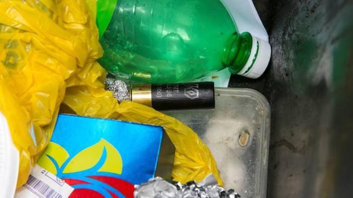 A blood-smeared bullet cartridge in a wheelie bin at Cody Hiri's house.
